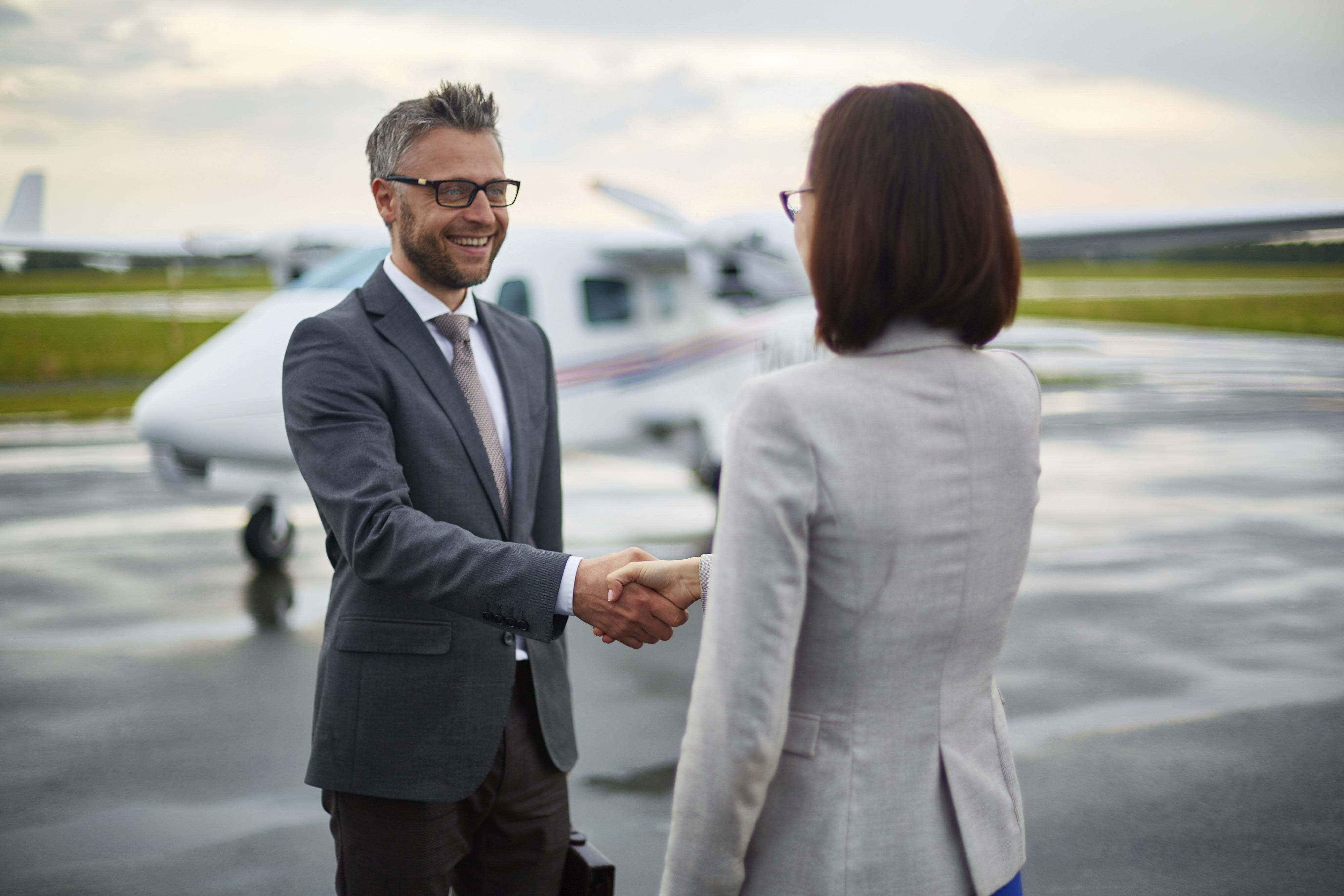Happy businessman handshaking with his partner in airport